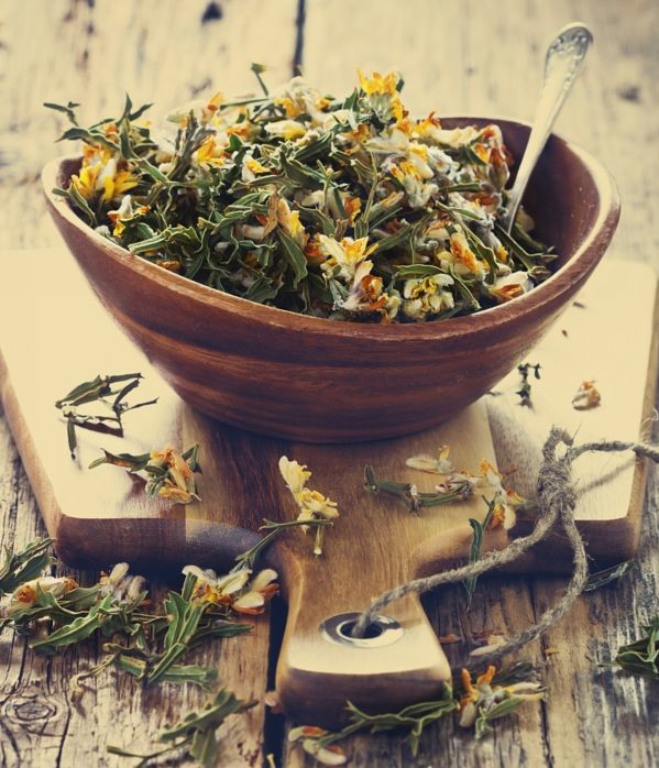 Dried medicinal herbs in a bowl on a wooden table.( Carqueja and Genista Tridentata). Alternative treatment . Selective focus. Toned image