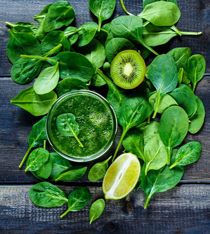 Rustic background with healthy smoothie with green fruits and vegetables in a jar on dark wooden table. Detox, diet, health or vegetarian food concept. Top view.