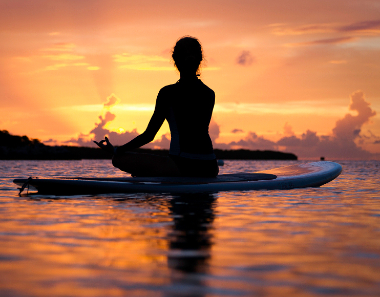 500px Photo ID: 106294703 - Enjoying the last minutes of daylight on a paddle board after practicing yoga
