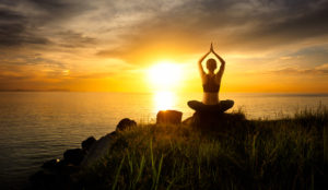 Woman meditating in a yoga pose on the beach at sunset