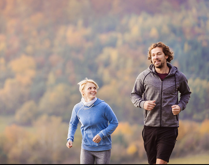Beautiful couple running outside in sunny nature